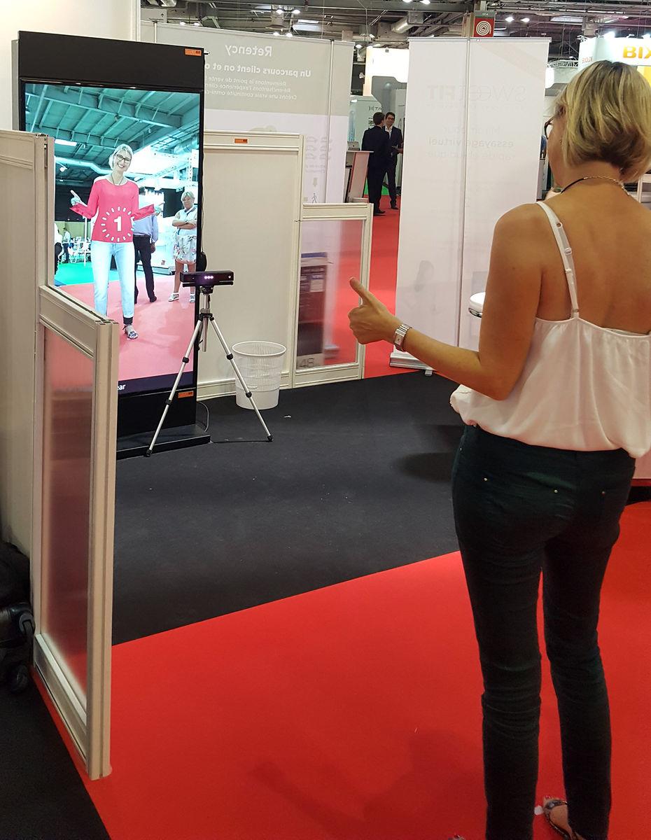Une femme essaye une tenue en cabine virtuelle